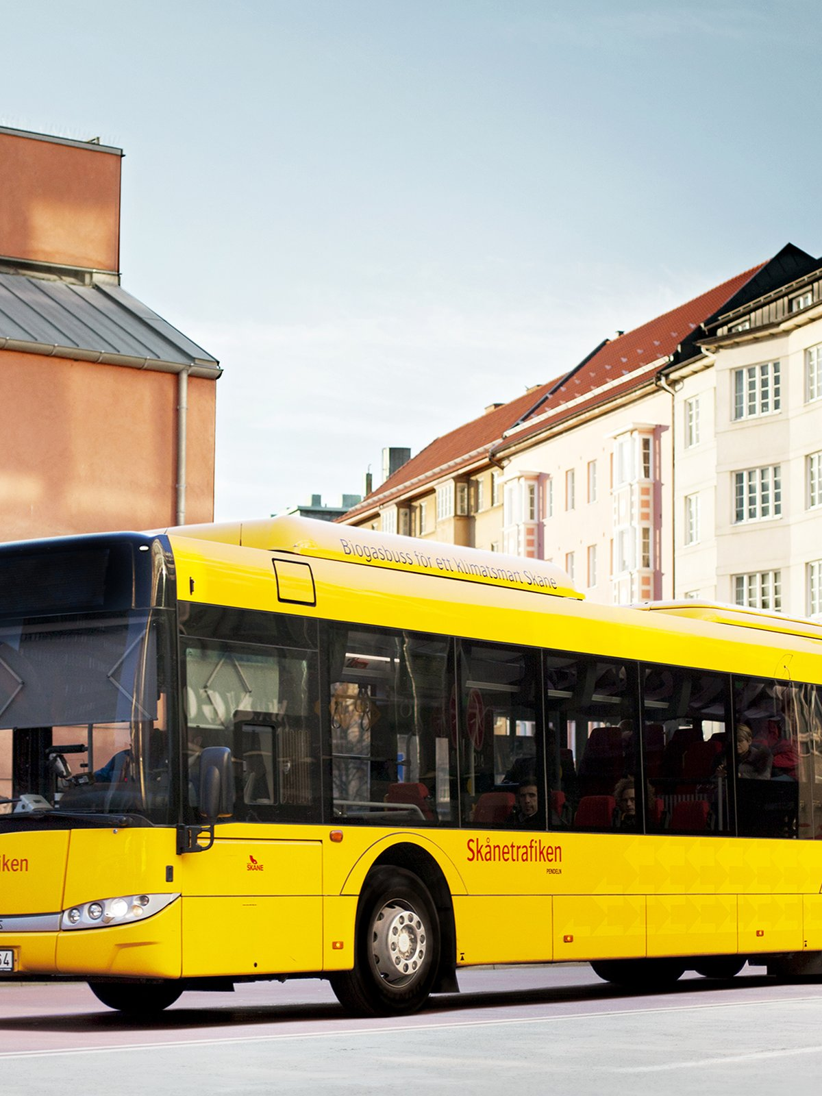 Yellow bus in front of buildings.
