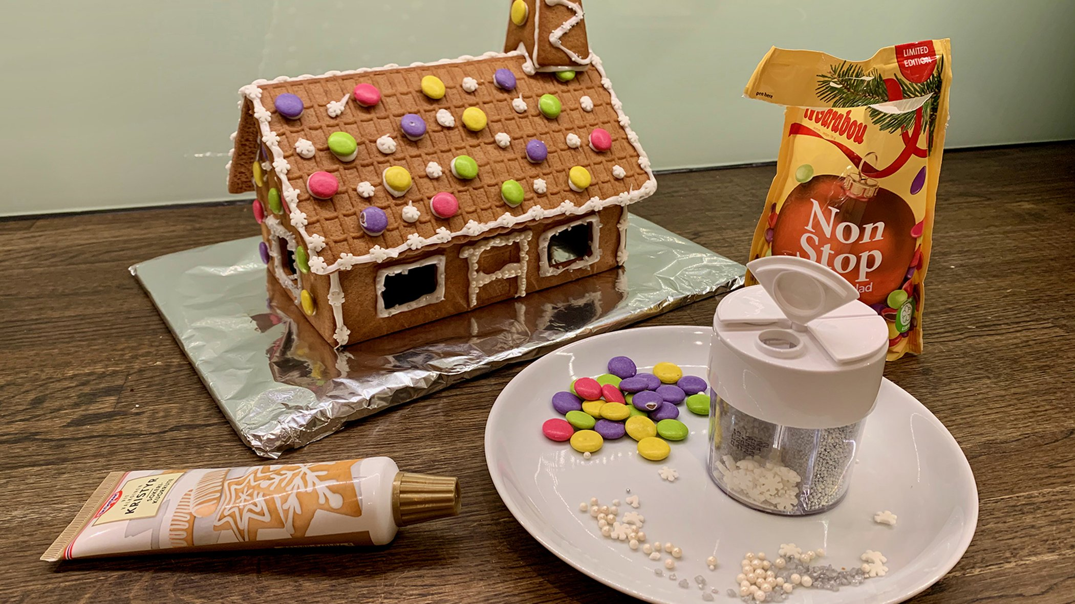 Newly finished gingerbread house along with candy decorations and frosting used to make it.