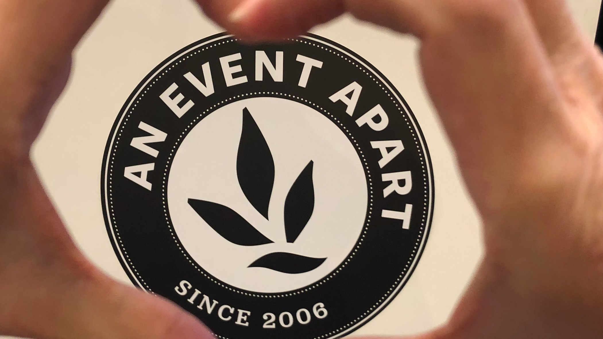 An Event Apart logo surrounded by two hands shaping a heart