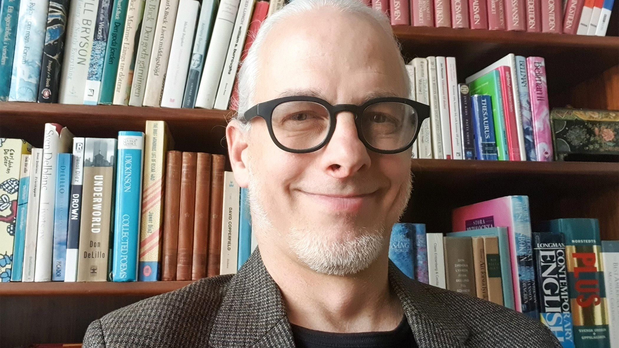 Person framför bokhylla, porträttfoto.