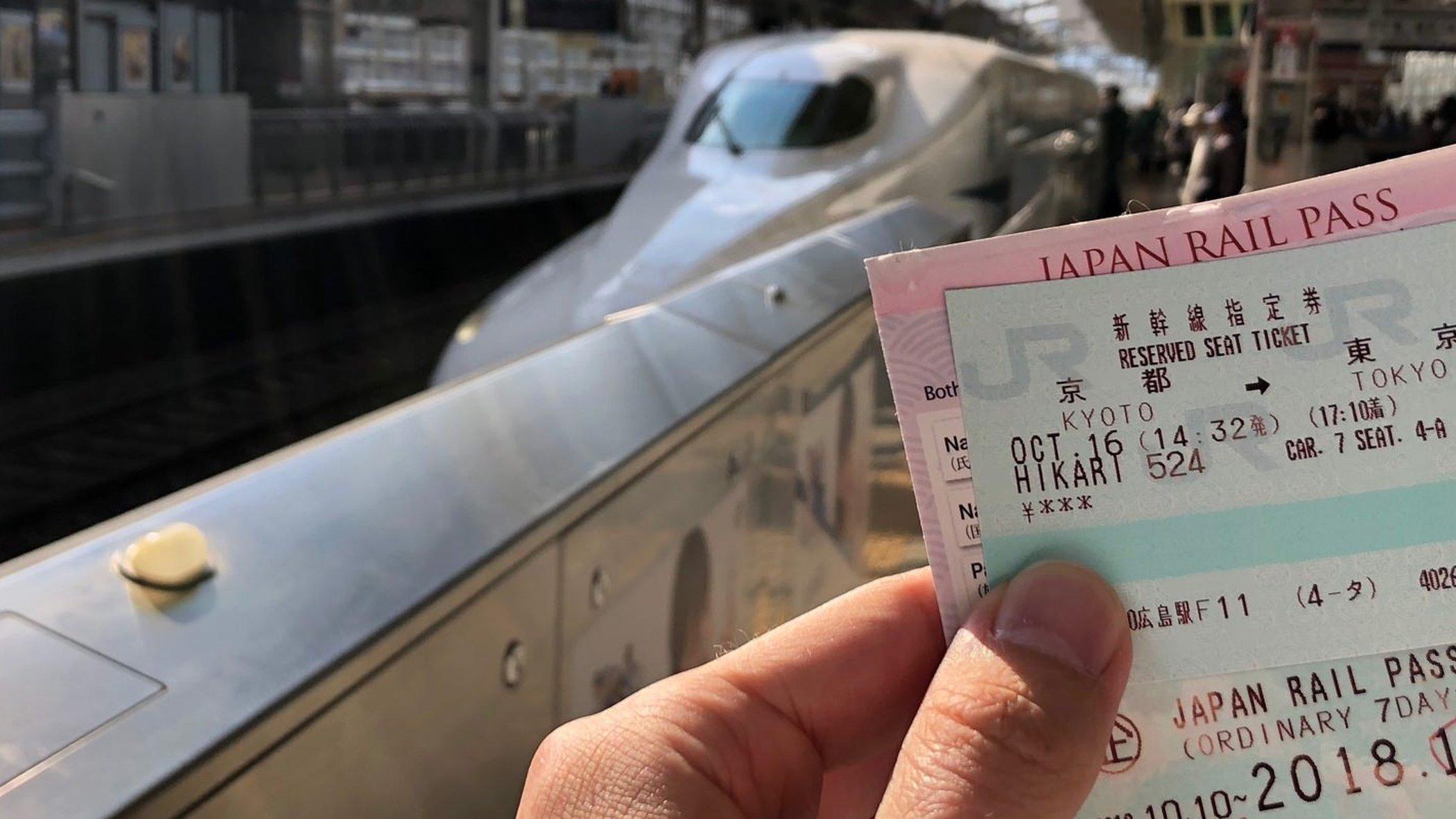 Ett Japan Rail Pass i handen med en tågplattform